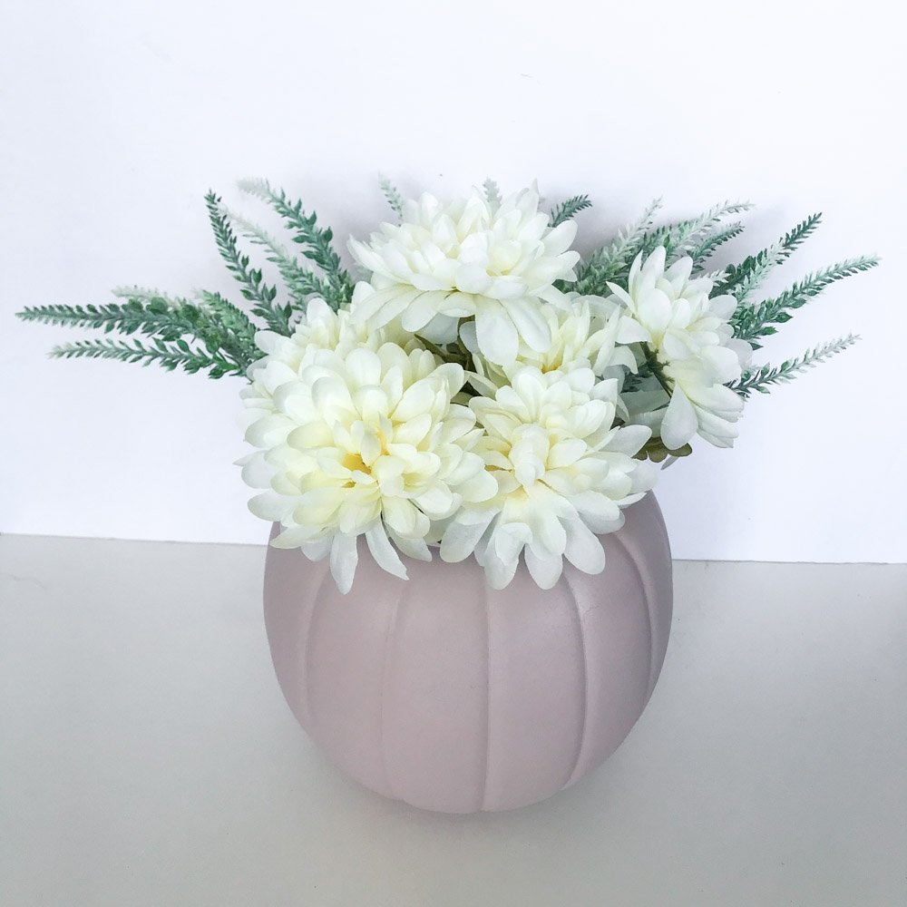 blush pink painted plastic pumpkin with white flowers